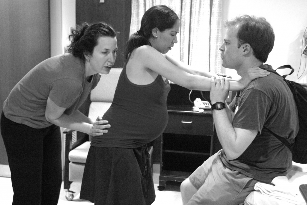 boober blog stages of labor. doula does sacral press while pregnant mother leans on father.