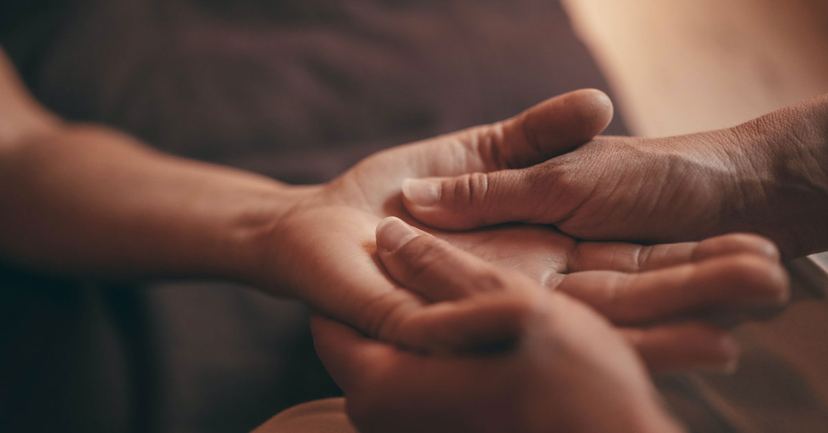 Image of a person holding another person's palm while giving it a massage