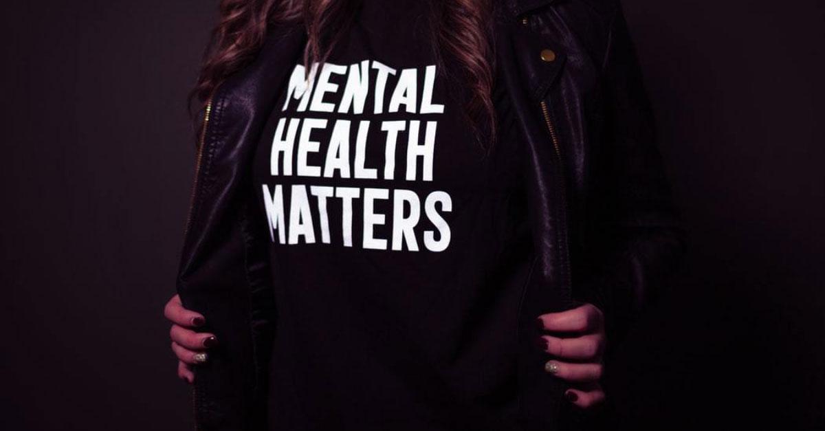 closeup image of a woman opening her jacket to display a mental health awareness shirt