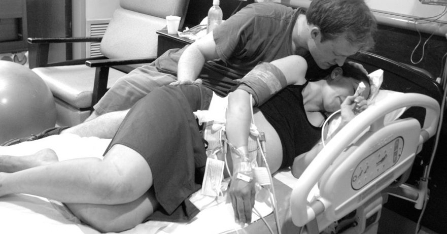 husband holding his wife while laying in a hospital bed